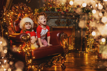 Happy siblings celebrate Christmas in beautiful decorated apartments. Time for miracles.