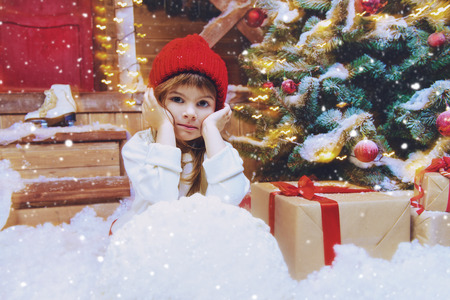 Pretty child girl is sitting near the house decorated for Christmas with a gift. Time for miracles. Merry Christmas and Happy New Year.