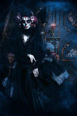Calavera Catrina sitting in interior. Sugar skull makeup. Dia de los muertos. Day of The Dead. Halloween.