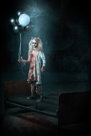 A scary girl standing on a bed with balloons. Halloween. Horror film.