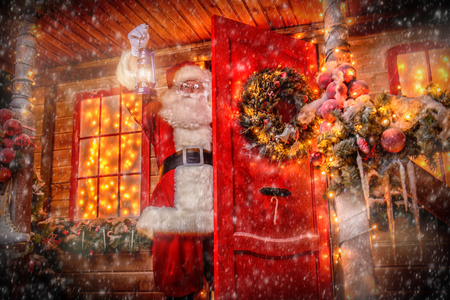Christmas concept. Portrait of a fairytale Santa Claus peek out from behind the door with lantern and wonders. Beautiful house decorated for Christmas. Time of miracles.