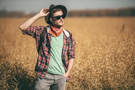 フィールド内の旅行者の肖像画。自然、自由。アクティブな男性のためのファッション。