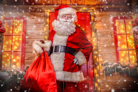 Portrait of good old Santa Claus holding a sack with gifts on the porch of his decorated house. House of Santa Claus. Christmas and New Year concept.