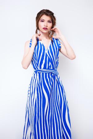Beautiful attractive girl wearing striped long dress posing in studio. Beauty, fashion. Studio shot. Stock Photo