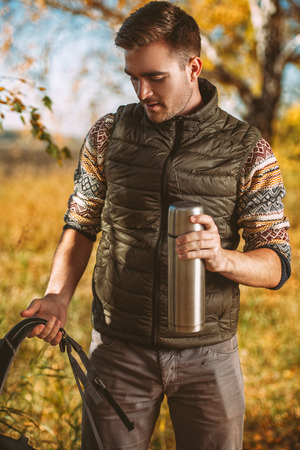 A portrait of a man drinking tea from a  in the countryside. Goods for travelling. Active lifestyle, autum fashion. Stock Photo