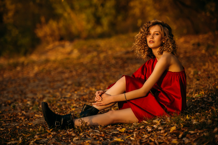 A beautiful young girl is posing in the countryside in a red dress. Fashion concept. Golden autumn.