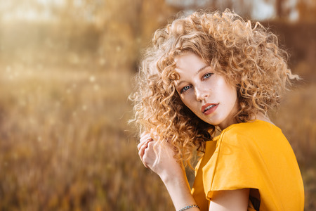 A portrait of a charming young girl with curly fair hair in a yellow dress. Fashion, beauty.