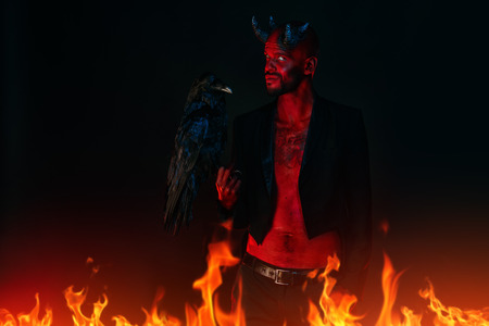 A portrait of a bad demon with a black raven. Horror movie, nightmare. Halloween. Stock Photo