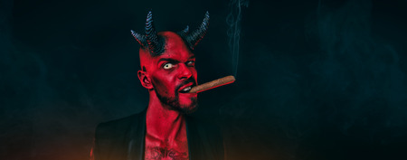 A close-up portrait of a bad demon with a cigar. Horror movie, nightmare. Halloween. 스톡 콘텐츠