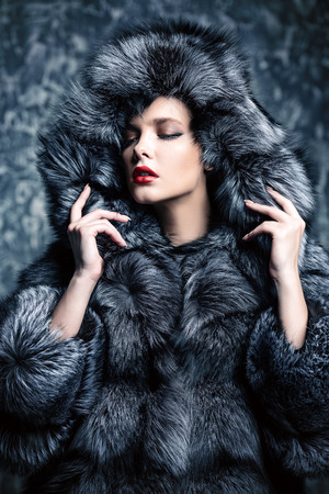 Beautiful woman in a fur coat with hood posing in studio. Luxury, rich lifestyle. Fashion shot. Stok Fotoğraf