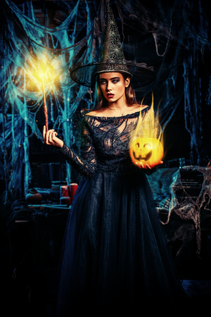 A witch in a castle holding a magic stick and a pumpkin. Halloween. Celebration.