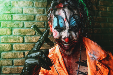 Halloween. Portrait of a disgusting clown man stained in blood over brick wall. Male zombie clown. Horror, thriller film. 스톡 콘텐츠