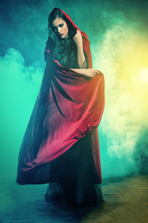 A beautiful lady in a red cloak. Halloween. Celebration. Stock Photo