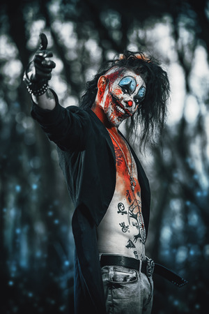 Scary punk clown man smeared with blood in a night forest. Halloween. Horror, thriller film.