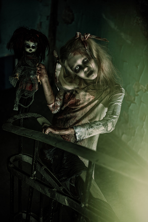 A portrait of scary zombie girl on the stairs with a toy. Halloween. Horror film.