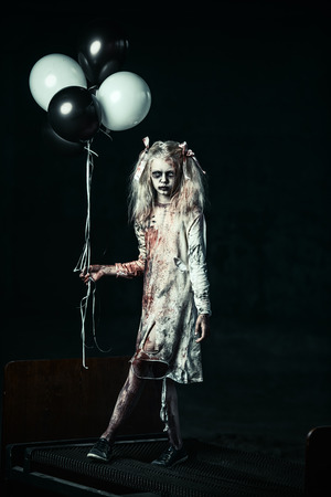 A scary zombie girl on a bed with balloons. Halloween. Horror film. Foto de archivo