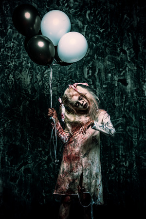 A scary zombie girl holding balloons. Halloween. Horror film.