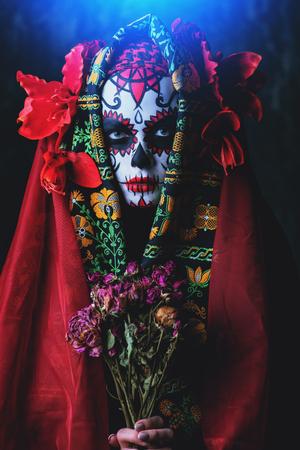 A portrait of Calavera Catrina holding a bouquet of flowers. Sugar skull makeup. Dia de los muertos. Day of The Dead. Halloween.