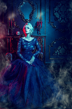 A beautiful vampire woman is sitting in a dark room. Classic style. Beauty, fashion.