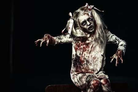 A portrait of a scary blonde zombie girl on a bed. Halloween. Horror film.