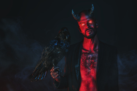 A portrait of a bad demon with a black raven. Horror movie, nightmare. Halloween. 스톡 콘텐츠