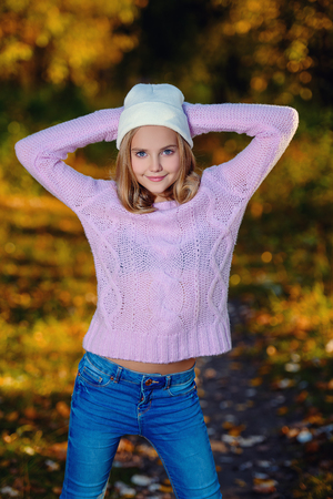 A portrait of a pretty young girl in the sunny forest. Autumn fashion, beauty.