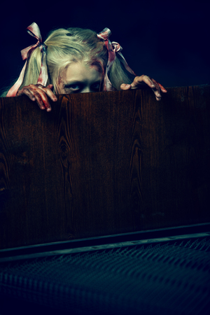 A portrait of a scary zombie girl looking from behind a bed. Halloween. Horror film.