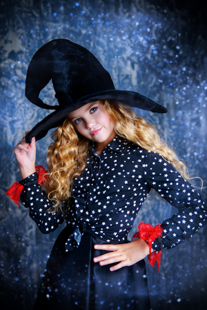 Beautiful child girl in a costume of a witch over grunge background. Halloween party. Stock fotó