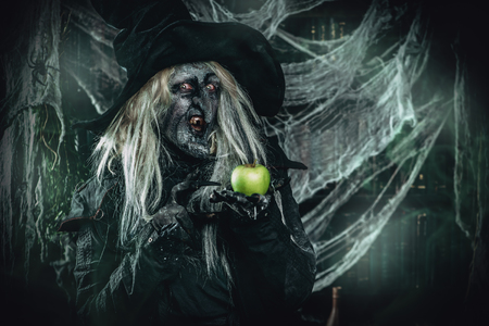 A witch holding an apple. Halloween. Horror movie.