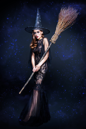A beautiful lady in a costume of witch. Halloween. Celebration.