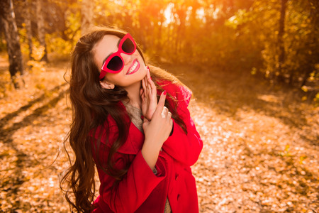 A portrait of a beautiful young woman wearing sunglasses in a sunny autumn forest. Lifestyle, autumn fashion, beauty.