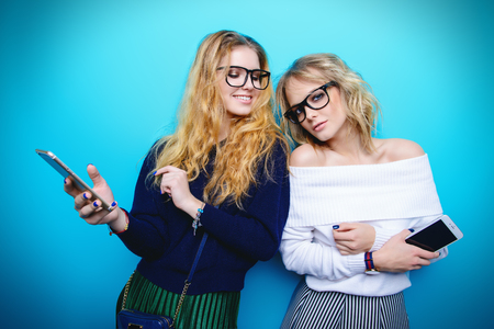 Two cheerful young women dressed in sweaters and skirts posing with telephones in the studio over blue background. Winter fashion.