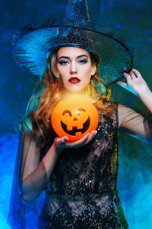 A beautiful lady in a costume of witch holding a pumpkin. Halloween. Celebration. Stock Photo