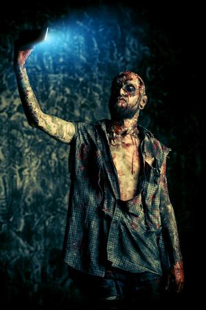 Gruseliger gruseliger Zombie macht ein Selfie. Halloween. Horrorfilm. Standard-Bild