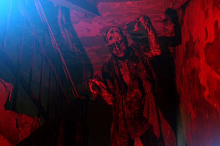 A portrait of a creepy scary zombie in red light. Halloween. Horror film.