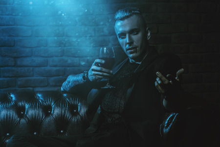 A vampire man is sitting in a dark room and drinking wine. Classic style. Beauty, fashion. Stock Photo
