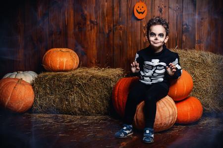Funny little boy in a skeleton costumes sitting on a big pumpkins Standard-Bild - 110767543