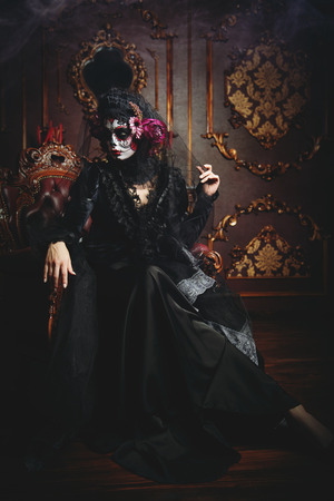 Calavera Catrina sitting in interior. Sugar skull makeup. Dia de los muertos. Day of The Dead. Halloween.