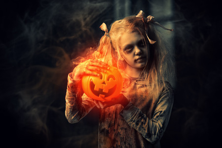 A portrait of a scary zombie girl with a pumpkin toy. Halloween. Horror movie.