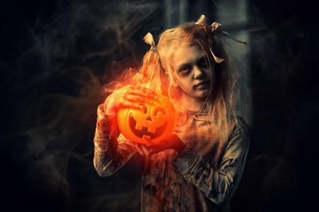 Een portret van een eng zombiemeisje met een pompoenstuk speelgoed. Halloween. Horrorfilm. Stockfoto