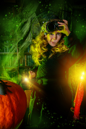 Happy Halloween. Cute child girl in witch costume is in a witch's lair. Cute funny witch girl wearing steampunk glasses. Standard-Bild - 110833493