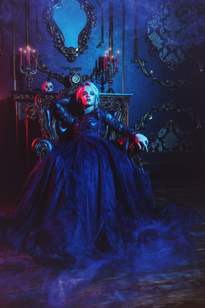 A vampire woman is in a dark room. Classic style. Beauty, fashion. 免版税图像