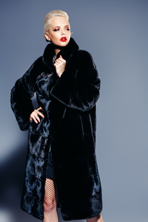 A portrait of a gorgeous blonde woman in luxurious black fur coat. Fashion, beauty. Studio shot. Stok Fotoğraf