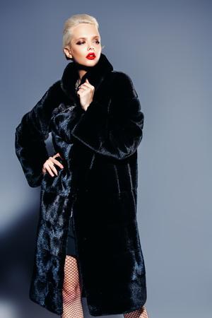 Un portrait d'une magnifique femme blonde en luxueux manteau de fourrure noire. Fashion beauté. Prise de vue en studio.
