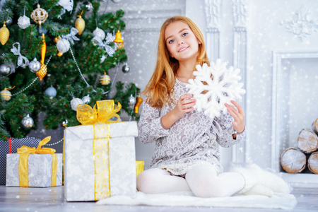 Pretty smiling girl in a Christmas room holding a snowflake. Merry Christmas and Happy New Year. Фото со стока