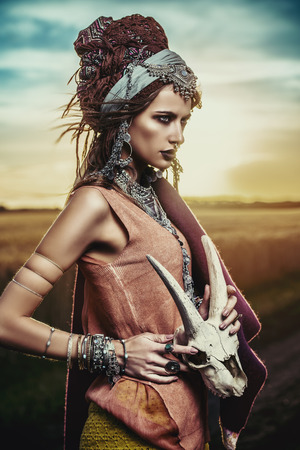 Magnificent gypsy fortune teller with a skull in the rays of the sunset. Stockfoto