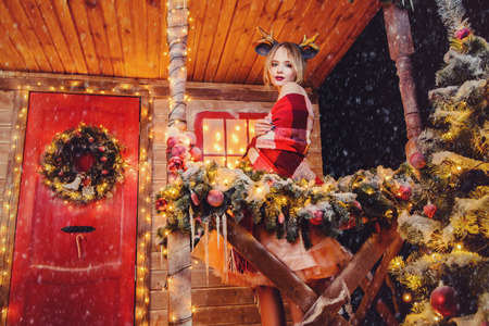 Happy girl in a deer horns on the head, wrapped in a blanket, stands near the house decorated for Christmas. Time for miracles. Merry Christmas and Happy New Year.