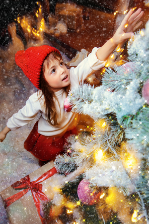 Pretty child girl is reaching for the toy hanging on the the Christmas tree. Time for miracles. Merry Christmas and Happy New Year. Banco de Imagens