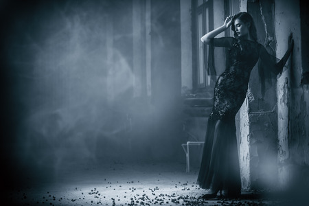 A beautiful brunette lady is in ruins. Evening dress. Fashion, beauty.