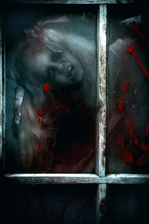 Scary little zombie girl behind the dirty window in blood. Halloween. Horror movie.